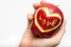 Η Apple, καρδιά, αγάπη στο χέρι γυναικών απομονώνει στο άσπρο υπόβαθρο Στοκ Εικόνες