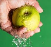 Η Apple σε δικοί του παραδίδει το νερό σε ένα πράσινο υπόβαθρο Στοκ φωτογραφίες με δικαίωμα ελεύθερης χρήσης