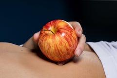 Η Apple στο στομάχι ενός νέου λεπτού κοριτσιού Στοκ φωτογραφία με δικαίωμα ελεύθερης χρήσης