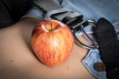 Η Apple στο στομάχι ενός νέου λεπτού κοριτσιού Στοκ Εικόνα