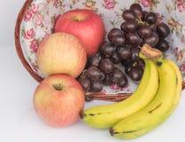 Η Apple, το σταφύλι και η μπανάνα είναι δροσερά αποτελέσματα φρούτων στο καλάθι Στοκ Εικόνα