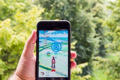 Η Apple iPhone6 συν κρατημένος σε ένα χέρι που παρουσιάζει οθόνη της με Pokemon πηγαίνει εφαρμογή Στοκ εικόνες με δικαίωμα ελεύθερης χρήσης
