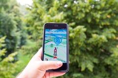 Η Apple iPhone6 συν κρατημένος σε ένα χέρι που παρουσιάζει οθόνη της με Pokemon πηγαίνει εφαρμογή Στοκ φωτογραφία με δικαίωμα ελεύθερης χρήσης