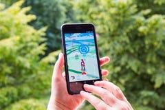 Η Apple iPhone6 συν κρατημένος σε ένα χέρι που παρουσιάζει οθόνη της με Pokemon πηγαίνει εφαρμογή Στοκ Εικόνες