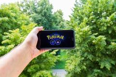 Η Apple iPhone6 συν κρατημένος σε ένα χέρι που παρουσιάζει οθόνη της με Pokemon πηγαίνει εφαρμογή Στοκ Φωτογραφίες