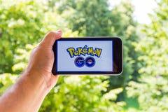 Η Apple iPhone6 συν κρατημένος σε ένα χέρι που παρουσιάζει οθόνη της με Pokemon πηγαίνει εφαρμογή Στοκ φωτογραφίες με δικαίωμα ελεύθερης χρήσης