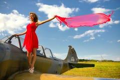 Η beautyful γυναίκα μόδας στο κόκκινο φόρεμα μένει σε ένα φτερό του παλαιού αεροπλάνου Στοκ Φωτογραφίες