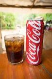 Η Coca-Cola μπορεί να πιει και ένα γυαλί του κοκ με τους κύβους πάγου Στοκ Φωτογραφίες