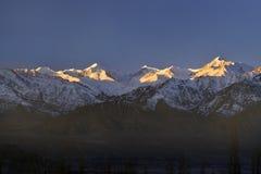Η Dawn στα βουνά, μια τεράστια σκοτεινή σειρά βουνών, χιονοσκεπείς άσπρες αιχμές φωτίζεται από το ρόδινο φως Στοκ φωτογραφίες με δικαίωμα ελεύθερης χρήσης