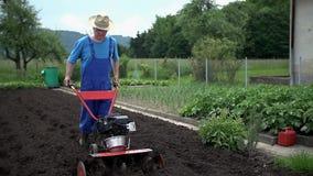 Η Farmer με ένα μεγάλο καπέλο οργώνει τον τομέα με τον καλλιεργητή απόθεμα βίντεο