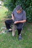 Η Farmer με το εργαλείο σφυριών και σιδήρου στο κολόβωμα δέντρων ακονίζει το δρεπάνι του στοκ φωτογραφία