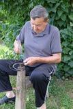 Η Farmer με το εργαλείο σφυριών και σιδήρου στο κολόβωμα δέντρων ακονίζει το δρεπάνι του στοκ φωτογραφίες με δικαίωμα ελεύθερης χρήσης