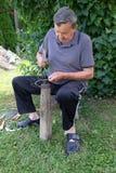 Η Farmer με το εργαλείο σφυριών και σιδήρου στο κολόβωμα δέντρων ακονίζει το δρεπάνι του στοκ φωτογραφίες