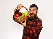 Η Farmer με το συγκινημένο πρόσωπο παρουσιάζει τα μήλα, τα σταφύλια και τα τα βακκίνια στοκ φωτογραφία