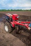 Η Farmer οργώνει το έδαφος με έναν καλλιεργητή, που προετοιμάζει το για τη φύτευση των λαχανικών Στοκ φωτογραφία με δικαίωμα ελεύθερης χρήσης