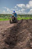 Η Farmer οργώνει το έδαφος με έναν καλλιεργητή, που προετοιμάζει το για τη φύτευση των λαχανικών Στοκ Εικόνες