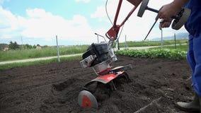 Η Farmer προσθέτει ένα ζευγάρι των εφεδρικών μικρών ροδών στον καλλιεργητή απόθεμα βίντεο