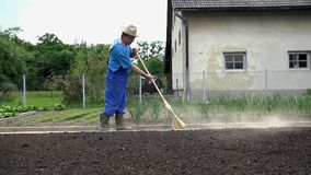 Η Farmer σκουπίζει το πάτωμα με μια μεγάλη σκούπα στην πορεία στον κήπο του απόθεμα βίντεο