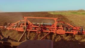 Η Farmer στα άροτρα Ρωσία τρακτέρ steadicam νεύει το χώμα γεωργίας το έδαφος προετοιμάζοντας το έδαφος με τον καλλιεργητή φυτωρίω απόθεμα βίντεο