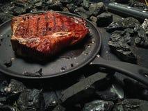 Η Juicy μπριζόλα βρίσκεται στο πετρέλαιο στο τηγανίζοντας τηγάνι Στοκ Φωτογραφίες
