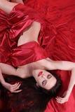 Η Nude γυναίκα στο κόκκινο σατέν καλύφθηκε σεντόνια Στοκ εικόνες με δικαίωμα ελεύθερης χρήσης