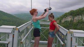 Η Redhead καυκάσια παλαιότερη αδελφή βγάζει τα γυαλιά εικονικής πραγματικότητας από νεώτερο ξανθό ενάντια στην κοιλάδα βουνών απόθεμα βίντεο