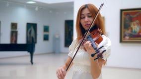 Η Redhead κυρία σε ένα άσπρο φόρεμα παίζει το βιολί απόθεμα βίντεο