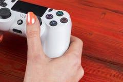 Η Sony PlayStation 4 ελεγκτής παιχνιδιών dualshock στα gamers δίνει στον ξύλινο πυροβολισμό στούντιο υποβάθρου Κονσόλα παιχνιδιών Στοκ εικόνες με δικαίωμα ελεύθερης χρήσης