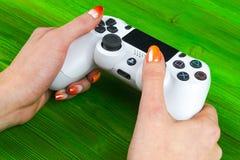 Η Sony PlayStation 4 ελεγκτής παιχνιδιών dualshock στα gamers δίνει στον πράσινο πυροβολισμό στούντιο υποβάθρου Στοκ Φωτογραφία