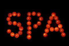 Η SPA επιγραφής των κόκκινων κεριών σε ένα σκοτεινό υπόβαθρο Στοκ Εικόνα
