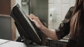 Η swiping πιστωτική κάρτα σερβιτόρων γυναικών μέσω του τερματικού υπολογιστών στον καφέ και επιλέγει φιλμ μικρού μήκους