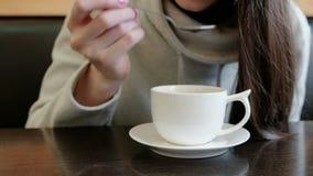 Η Unrecognizable γυναίκα πίνει το καυτό τσάι από το φλυτζάνι με ένα κουτάλι Κλείστε επάνω τα χέρια και το στόμα απόθεμα βίντεο