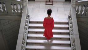 Η Unrecognizable γυναίκα στο κόκκινο φόρεμα στα υψηλά τακούνια αναρριχείται σε μια μεγάλη σκάλα φιλμ μικρού μήκους