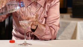 Η Unrecognizable συνταξιούχος γυναίκα κάθεται στο νερό εστιατορίων pouringstill από ένα μπουκάλι Έννοια τρόπου ζωής υγιής ζωή 4K φιλμ μικρού μήκους