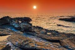 θάλασσα βράχων όμορφο ηλιοβασίλεμα τοπ Στοκ Φωτογραφία