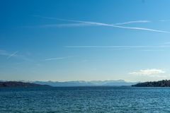 Θάλασσα και μπλε ουρανός την ηλιόλουστη ημέρα με τα όρη στο υπόβαθρο στη λίμνη Starnberg κοντά στο Μόναχο στη Γερμανία στοκ εικόνα