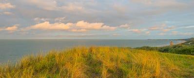 Θάλασσα κατά μήκος των αμμωδών αμμόλοφων λαμβάνοντας υπόψη την ανατολή Στοκ Φωτογραφία