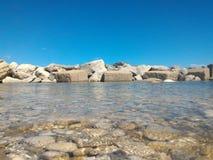 Θάλασσα με τους βράχους στον ορίζοντα στοκ φωτογραφία