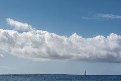 Θάλασσα ή ωκεάνιο νερό με το μπλε ουρανό, ένα sailboat και τα δραματικά σύννεφα Στοκ Εικόνες