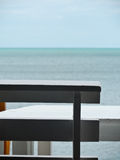 Θάλασσα και άσπρη καρέκλα με το μπλε ουρανό Στοκ Φωτογραφία