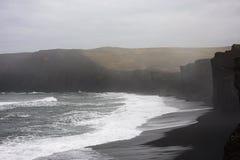 Θάλασσα μπροστά από τους μαύρους απότομους βράχους στοκ εικόνα