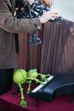 Θέατρο οδών - παιχνίδια μαριονετών βατράχων στο μικρό πιάνο Στοκ Φωτογραφία