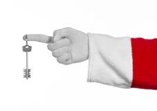 Θέμα Άγιου Βασίλη: Το santa χεριών κρατά τα κλειδιά σε ένα νέο διαμέρισμα ή ένα καινούργιο σπίτι σε ένα άσπρο υπόβαθρο Στοκ φωτογραφία με δικαίωμα ελεύθερης χρήσης