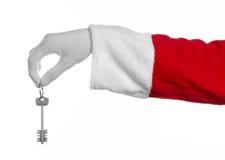 Θέμα Άγιου Βασίλη: Το santa χεριών κρατά τα κλειδιά σε ένα νέο διαμέρισμα ή ένα καινούργιο σπίτι σε ένα άσπρο υπόβαθρο Στοκ Εικόνες