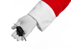 Θέμα Άγιου Βασίλη: Χέρι Santa που κρατά τα κλειδιά σε ένα νέο αυτοκίνητο σε ένα άσπρο υπόβαθρο Στοκ Εικόνα