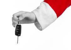 Θέμα Άγιου Βασίλη: Χέρι Santa που κρατά τα κλειδιά σε ένα νέο αυτοκίνητο σε ένα άσπρο υπόβαθρο Στοκ Φωτογραφίες
