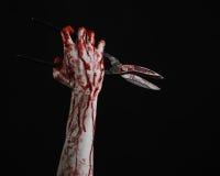 Θέμα αποκριών: αιματηρό χέρι που κρατά ένα μεγάλο παλαιό αιματηρό ψαλίδι σε ένα μαύρο υπόβαθρο Στοκ φωτογραφία με δικαίωμα ελεύθερης χρήσης