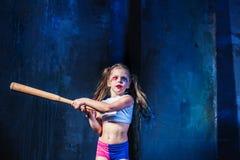 Θέμα αποκριών: Κορίτσι με το ρόπαλο του μπέιζμπολ έτοιμο να χτυπήσει Στοκ φωτογραφία με δικαίωμα ελεύθερης χρήσης
