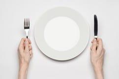 Θέμα εστιατορίων και τροφίμων: το ανθρώπινο χέρι παρουσιάζει χειρονομία σε ένα κενό άσπρο πιάτο σε ένα άσπρο υπόβαθρο απομονωμένη Στοκ Φωτογραφία