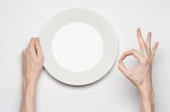 Θέμα εστιατορίων και τροφίμων: το ανθρώπινο χέρι παρουσιάζει χειρονομία σε ένα κενό άσπρο πιάτο σε ένα άσπρο υπόβαθρο απομονωμένη Στοκ φωτογραφία με δικαίωμα ελεύθερης χρήσης